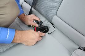 lift up on the seat bottom to expose the clasp there will be a handle that gets pulled to release the front of the seat bottom