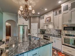 kitchen with polished granite counters and white cabinets with a light blue island