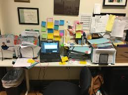 office desk space. Cluttered Office Desk Space Filled With Folders And Post-its