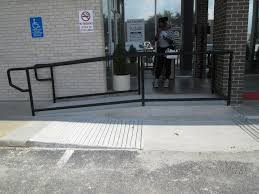 the curb ramp is the one that crossed a curb at the parking spaces the ramp in the background is part of the entry and does not cross the curb