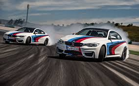 two white red and blue coupes bmw m4 race tracks