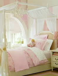 girls canopy bed with white curtain and crystal chandelier also pink accent bedding set