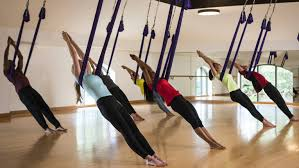 group of people lean back on small hammocks from ceiling in anti gravity yoga session