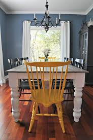antique old black iron farmhouse style chandeliers lighting above reclaimed wood dining table painted with white chalk paint color and high back dining