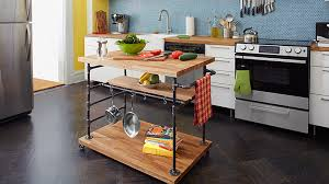 take your old plastic cutting board to the chopping block and upgrade your kitchen with this island on wheels with a large countertop two shelves below