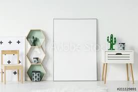 small cupboard with cactus shaped lamp and decorative box standing in white baby room interior with empty poster with place for your graphic wooden chair