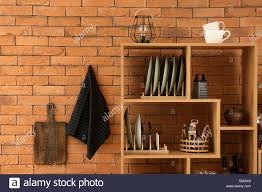 set of clean dishes with utensils on wooden shelves near brick wall