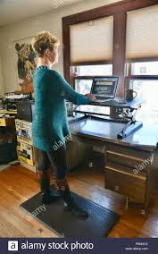 Home office standing desk Motorized Middleage Business Woman Standing And Working On Apple Macbook Pro Using Flexispotloctek Ergonomic Standing Desk At Home Office Browntown Wi Usa Art Of Trying Middleage Business Woman Standing And Working On Apple Macbook Pro