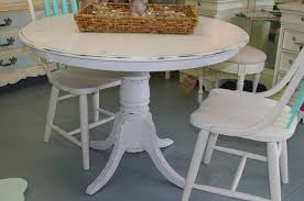 unique distressed white round kitchen table with 3 white chairs and rattan wicker serving tray