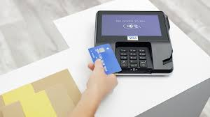 hand holding a visa credit card at a pos machine