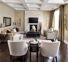decorating a long narrow living room with fireplace under flat screen tv and using black leather square ottoman coffee table also white ceiling designs