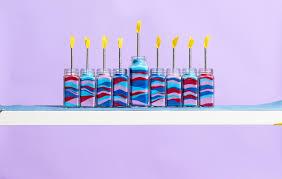 handmade hanukkah menorahs in multi colored jars on shelf against purple background