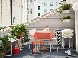 a balcony furnished with a small foldable table a bench and two chairs all balcony furnished small