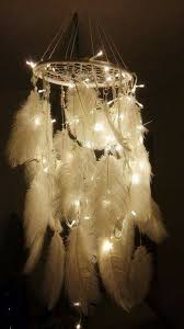 a diy chandelier made from hula hoop twine lights and plumes is a