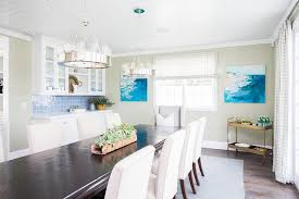 long dark stained dining table with cream upholstered chairs lit by a set ralph lauren roark modular ring chandeliers in front of a window flanked by blue