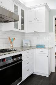 beautiful kitchen features white cabinets paired with fantasy brown granite countertops in a leather finish alongside half the wall clad in subway tiles and