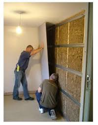 sound insulation for walls. Two Men Installing A Studio Wall System By Fixing Acoustic Plasterboard To Resilient Bars On Stud Sound Insulation For Walls E