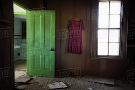 room inside an old abandoned house with a green door open and an old dress hanging on the wall united states of america