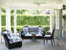 image black wicker outdoor furniture. covered patio features a beadboard ceiling accented with fan over black wicker outdoor sofa lined blue cushions and chevron pillows as image furniture n