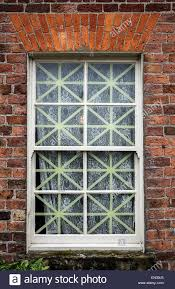 old fashioned ww2 era window with net curtains and tape to minimise damage