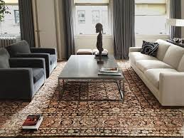antique persian oriental rug with grey sofa interior design by denise kuriger