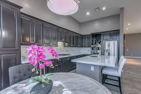 dark gray kitchen cabinets and gray painted walls and island with white quartz countertop
