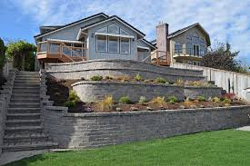 this massive 4 tier retaining wall includes an integrated stairway landscaping and a paver patio above the top tier