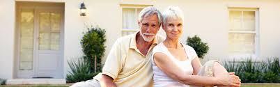 un couple de senior devant une maison