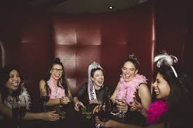 playful carefree young female millennial friends drinking enjoying bachelorette party at nightclub
