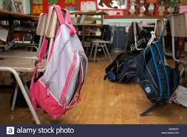 classroom chair back. stock photo - girls and boys schoolbag rucksacks hanging off the back of empty classroom chairs in primary school belfast northern ireland chair s