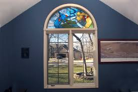 arched transom stained glass window with cardinal and fighter jet