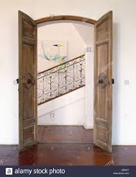 old carved wood double doors open in french country hall with view of wrought iron banisters on staircase