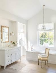 mini french chandelier hanging over wainscoted bathtub