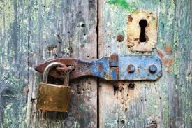 old lock and rusted keyhole on green wooden door