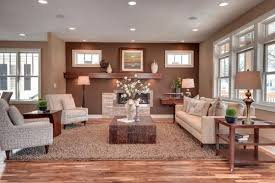 this open plan living room smartly uses a light brown rug to diffeiate the living room from the kitchen