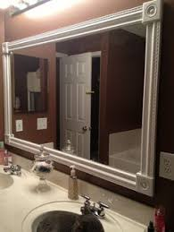 white framed bathroom mirror. diy bathroom mirror frame. white styrofoam molding, wood corner squares, and a craft framed e
