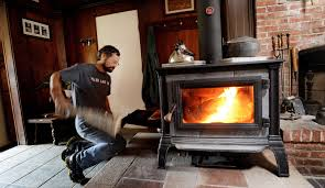 steve fuller of peru feeds his new equinox wood stove he and his wife