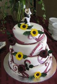 Round Four Tier White Wedding Cake With Sunflowers And Bride And