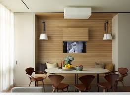 In this apartment, the television was placed behind a panel within the  walnut wall,