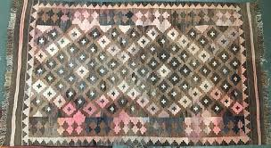 a small brown and pink kilim rug