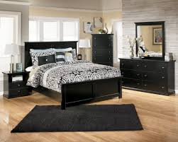 bedroom black wooden bed with black bedding set and black rug on brown wooden floor