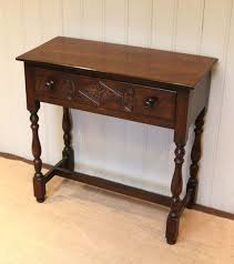 small oak side table having a single drawer with a carved front and turned wooden handles raised on turned legs united by an understretcher