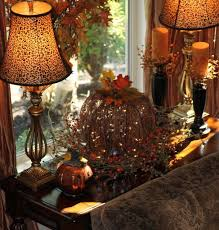 Fall decor / a big light up pumpkin center stage on a table, planked by two  lamps, added two candles, and a metal pumpkin on the other side.