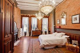 luxurious brick walled bedroom with twin chandeliers ideas