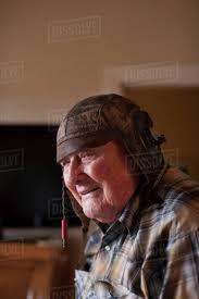 senior man indoors wearing old leather football helmet