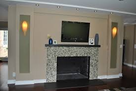 stunning fireplace with stacked stone surround and brown varnished scenic grey glass tiles mosaic surrounds dark finish wooden mantel piece