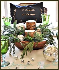 rustic tablescape with rustic bich style candles and evergreens in a wood bread bowl
