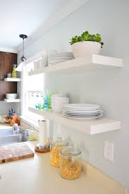 two pairs of white ikea lack shelves hung in the kitchen with white plates bowls