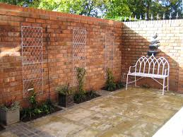 reclaimed brick walls in a small courtyard garden from a garden design by sue davis outside rooms co uk