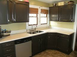 black wooden kitchen cabinet and white granite countertopc connected by glass windows with brown window blinds